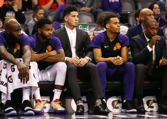Phoenix Suns guard Devin Booker sits out the game with injury against the Sacramento Kings in the first half on Jan. 8 at Talking Stick Resort Arena