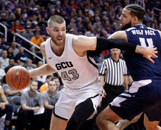 Grand Canyon's Michael Finke (43) pushes his way around Nevada's Cody Martin (11) during the first half of an NCAA college basketball game Sunday, Dec. 9, 2018, in Phoenix. (AP Photo/Darryl Webb)