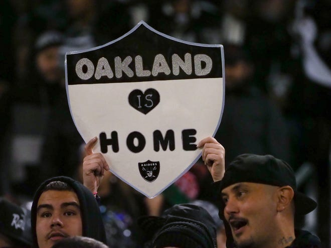 "An Oakland Raiders fan holds a sign reading ""Oakland is home"" during the third quarter against the Denver Broncos at Oakland Coliseum."