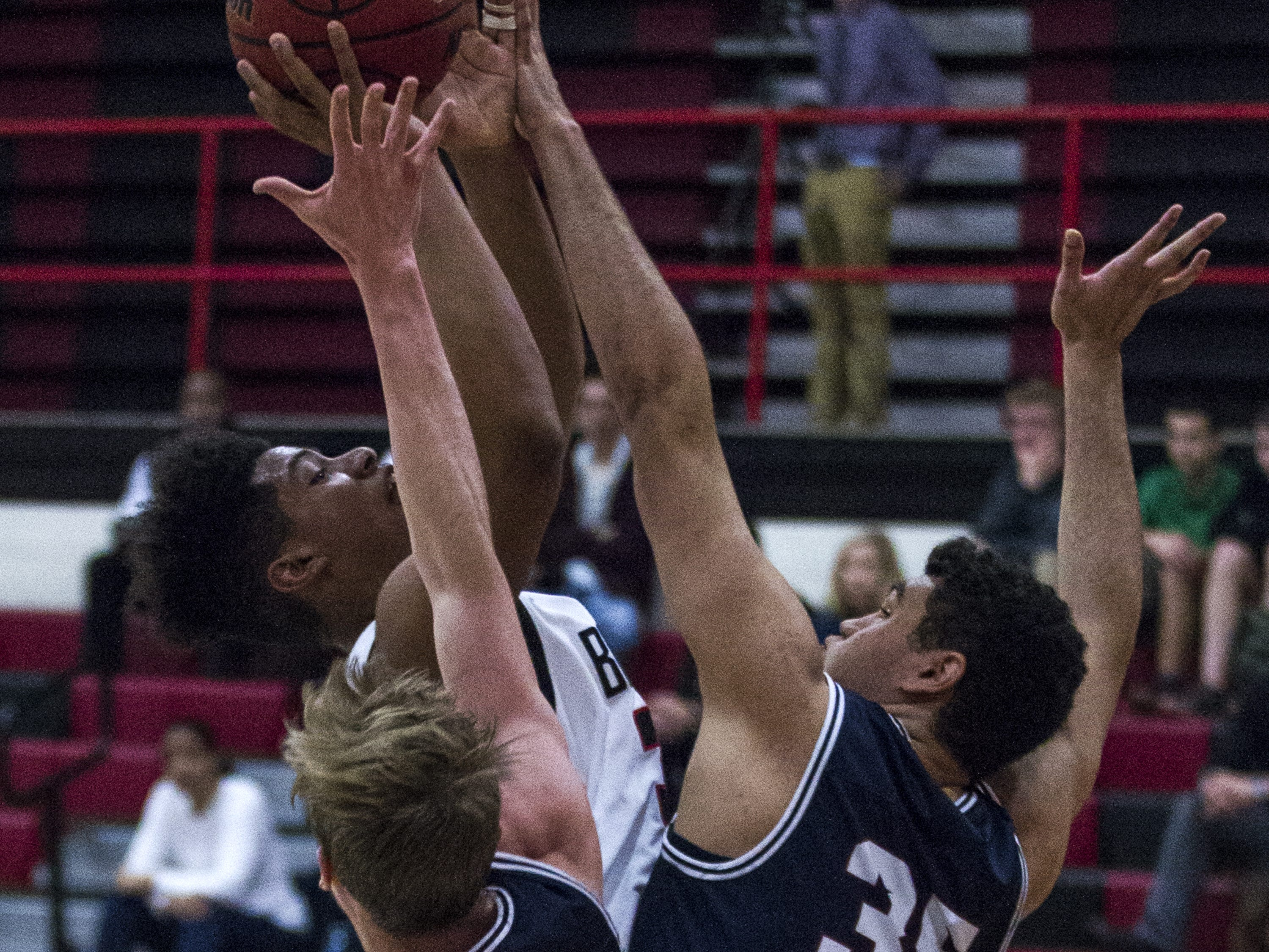 Brophy's Arnold Dates (30) puts up a shot against Perry's Andrew Morrill (4) and Miles Houston (35) during in the first half of their game at Brophy High School in Phoenix, Tuesday, Jan. 8, 2019.