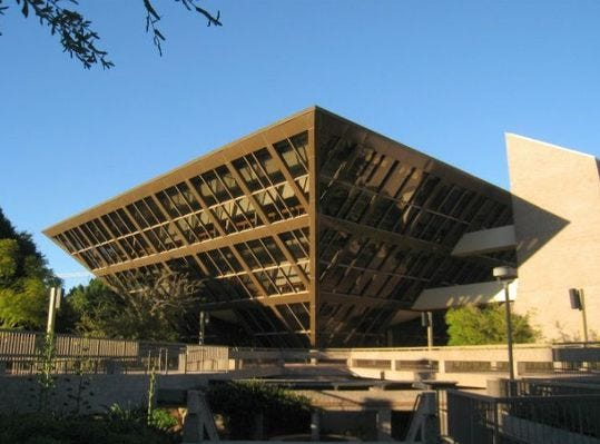 Tempe City Hall is known for its striking inverted-pyramid shape, with tinted glass walls angled at 45 degrees so every window naturally has shade. Inside, it's round, with an elevator in the center and offices around the sides. The pyramid is surrounded by a sunken garden; platforms and walkways lead pedestrians into the garden level and across it to the building entrances.It was built on the site of the former City Hall, which was built in 1914, but demolished when city leaders believed both the building and downtown area to be deteriorating. They proposed moving the building south, but City Council voted 4-3 to stay downtown. The subsequent building became a symbol of the city's confidence in downtown and pushed Mill Avenue and the rest of downtown toward redevelopment.