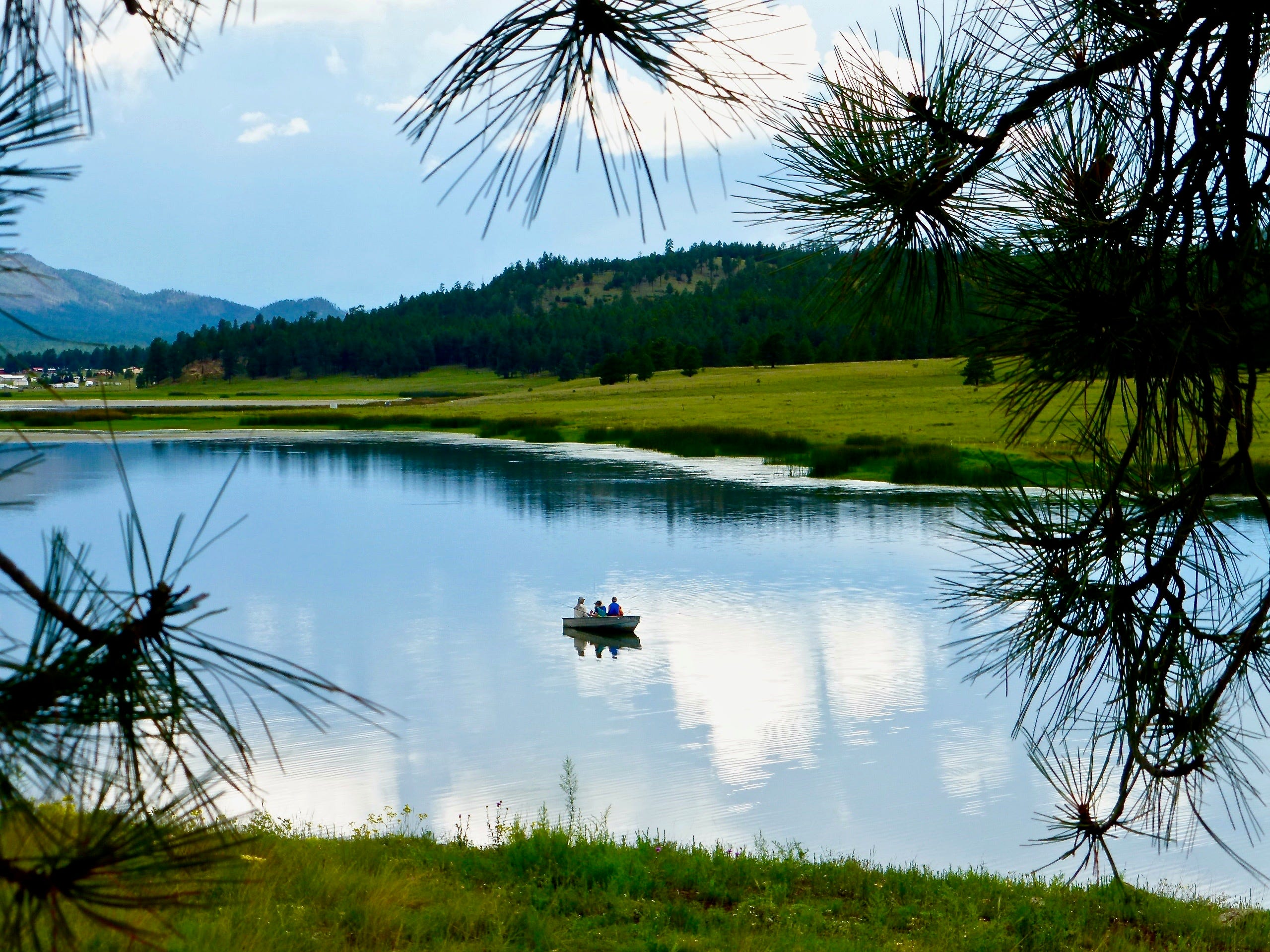 Anglers try their luck at Luna Lake, with the small town of Alpine visible in the distance.