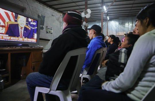 Migrantes en Tijuana escuchan frente a una televisión el mensaje de Donald Trump.