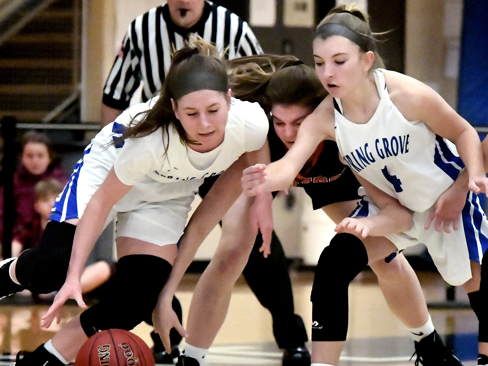 Spring Grove's Ellie Glass, left, and Addyson Wagman chase a loose ball with Central York's Zada Stockbower during basketball action at Spring Grove Tuesday, Jan. 8, 2019. Bill Kalina photo
