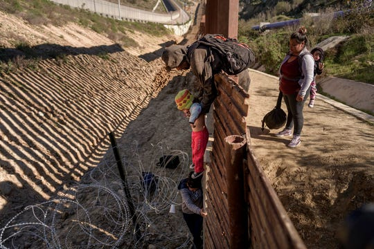 FILE - In this Saturday, Dec. 29, 2018, file photo, a man passes a Mexican migrant baby to her mother after they jump the border fence to get to the U.S. side to San Diego, from Tijuana, Mexico. (AP Photo/Daniel Ochoa de Olza, File)