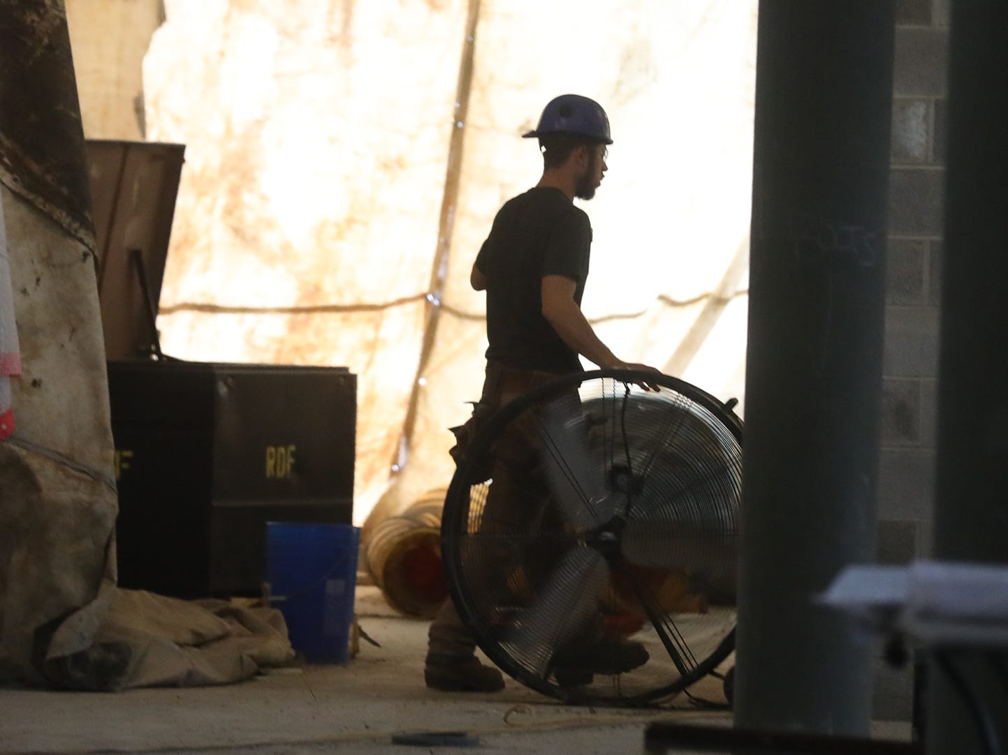 A construction worker passes through to an area he is working in.