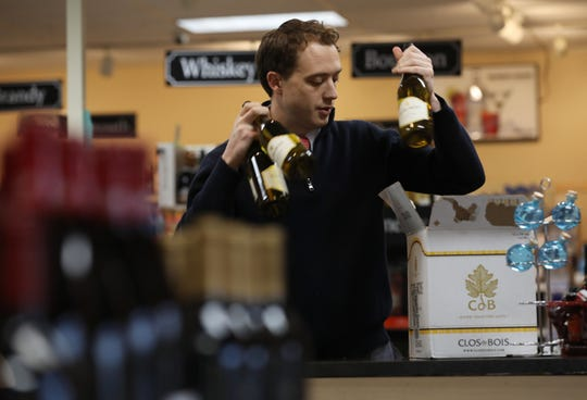 Matt Yaeger, co-owner and general manager of Pinnacle Wine and Liquor in Brighton, fills an online order in his store. Yeager is among the retailers who favors expanding wine shipping.