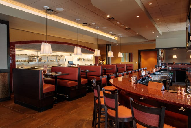 110 Grill features a horseshoe-shaped bar and an open kitchen.