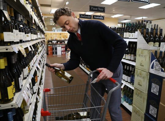 Matt Yaeger, co-owner and general manager of Pinnacle Wine and Liquor in Brighton, fills an online order in his store.