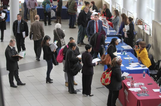 File photo: A line of people wait to speak to recruiters with the University of Rochester during a job fair at the War Memorial at the Blue Cross Arena.