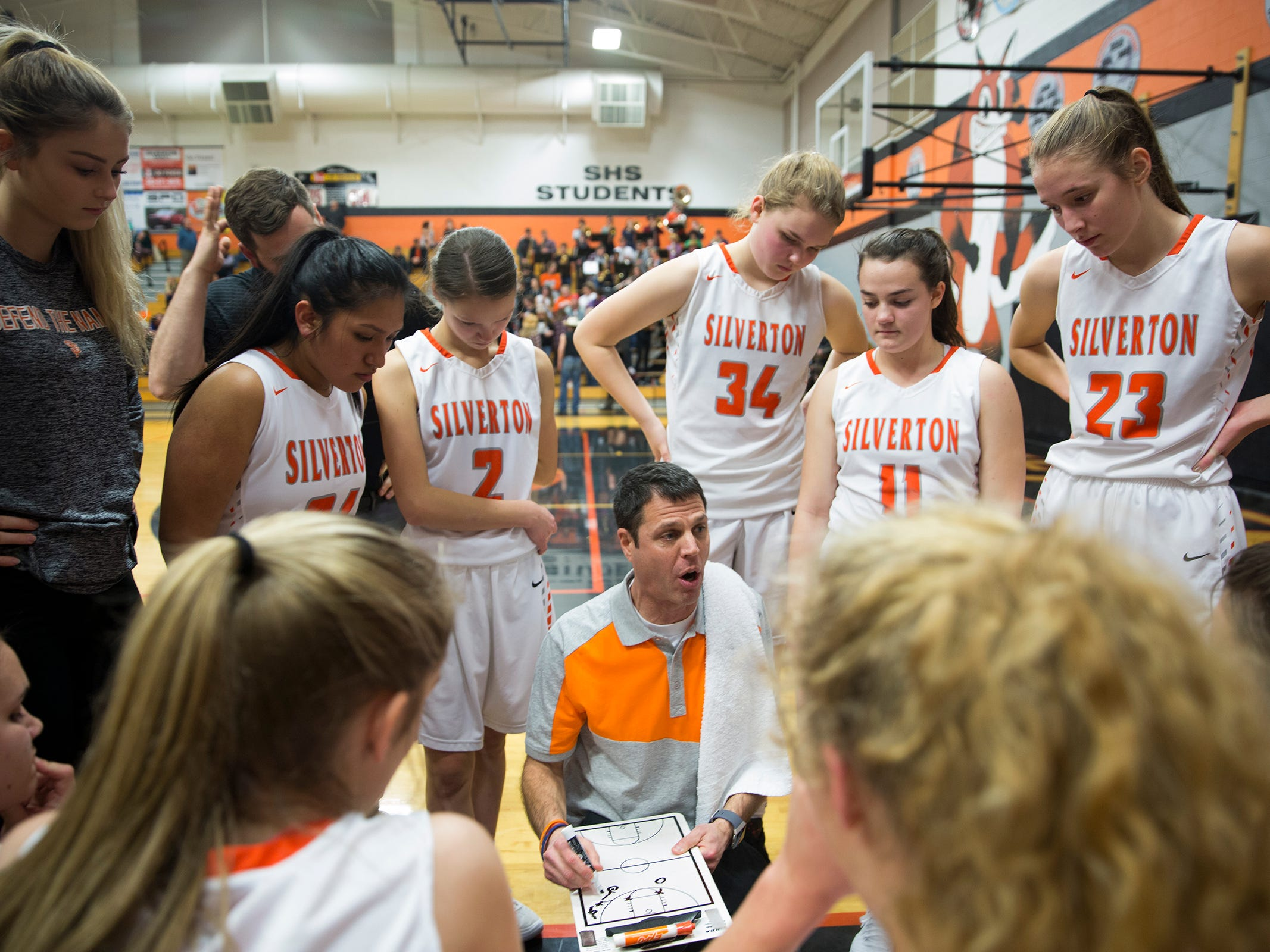 Silverton head coach Tal Wold goes over a play with his team during the Dallas High School vs. Silverton High School girls basketball game in Silverton on Tuesday, Dec. 8, 2019.