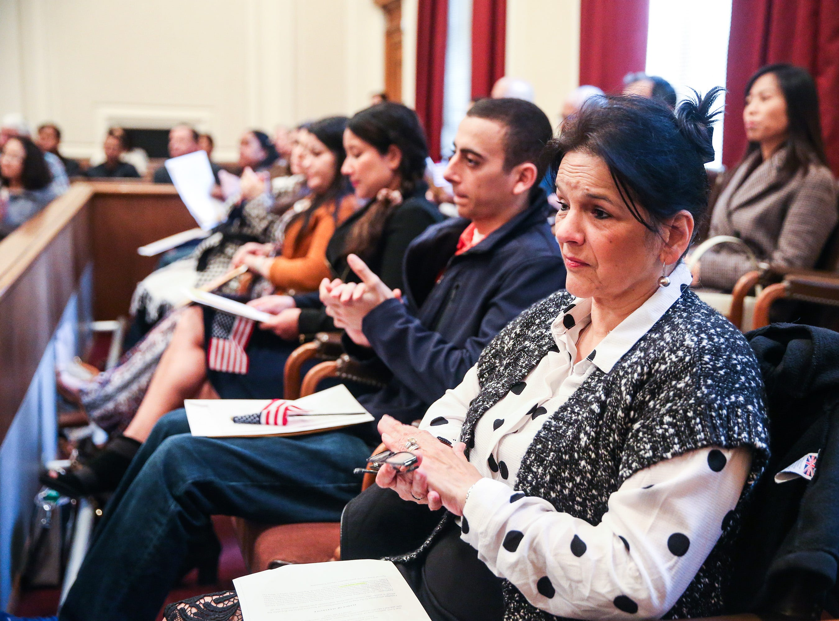 Applicants listen to a speaker during the naturalization ceremony Wednesday, Jan. 8, 2019, at the O.C. Fisher Federal Building.