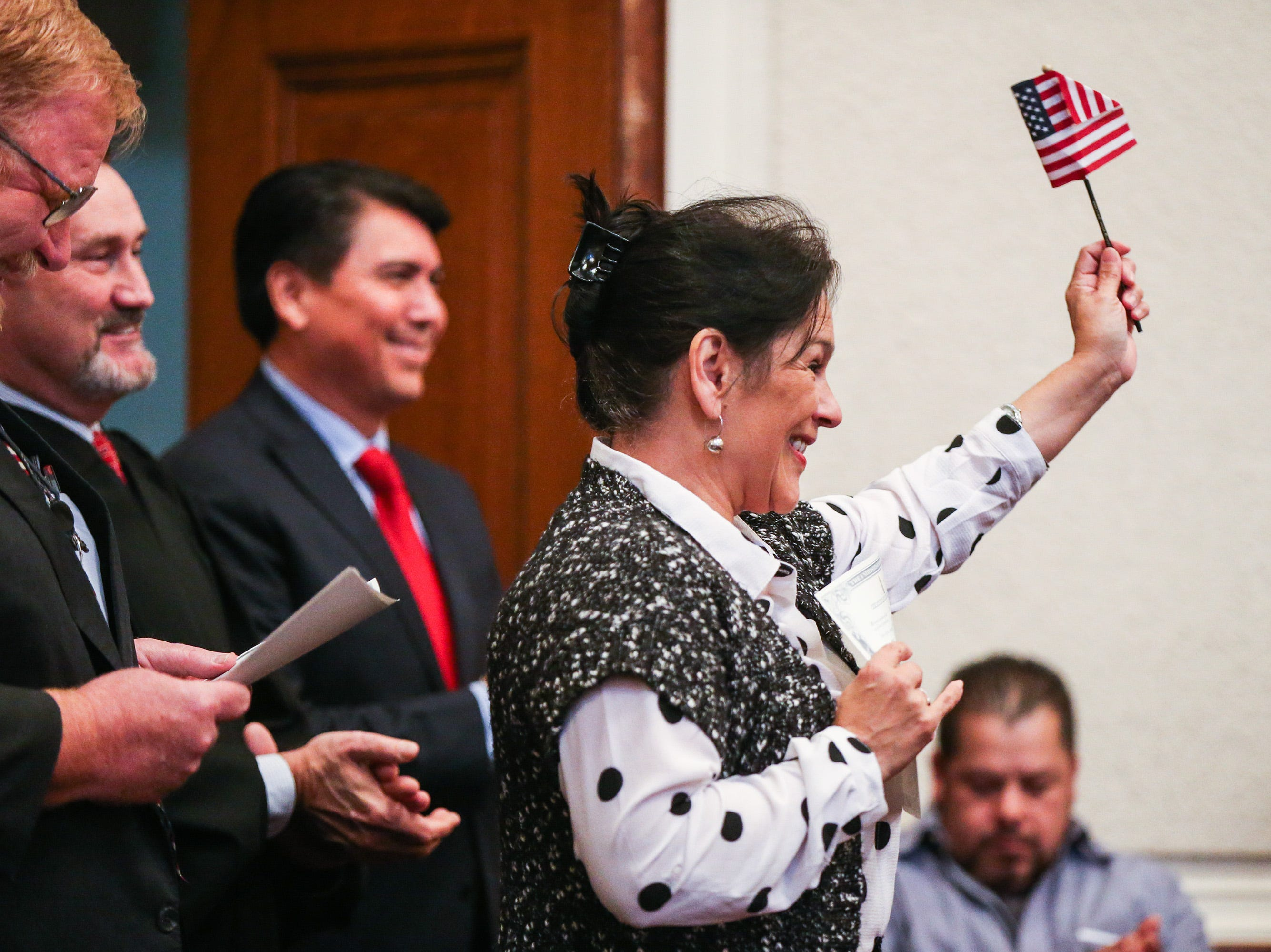 Christine Anita Sawyer waved a flag after she receives her certificate during the naturalization ceremony Wednesday, Jan. 8, 2019, at the O.C. Fisher Federal Building.