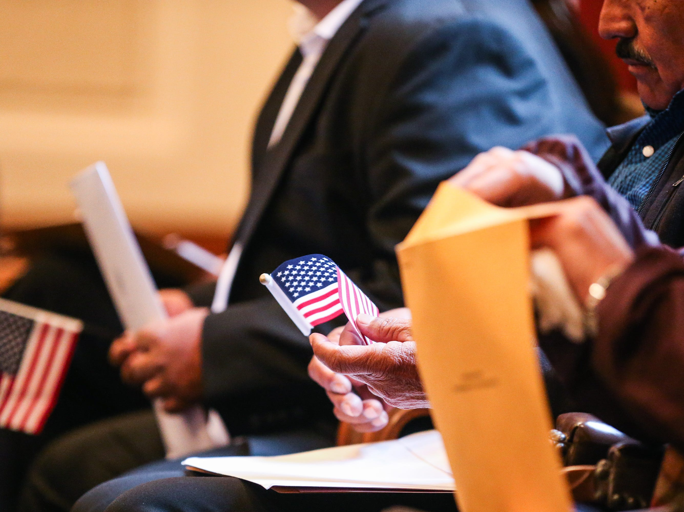 An applicant holds a flag during the naturalization ceremony Wednesday, Jan. 8, 2019, at the O.C. Fisher Federal Building.