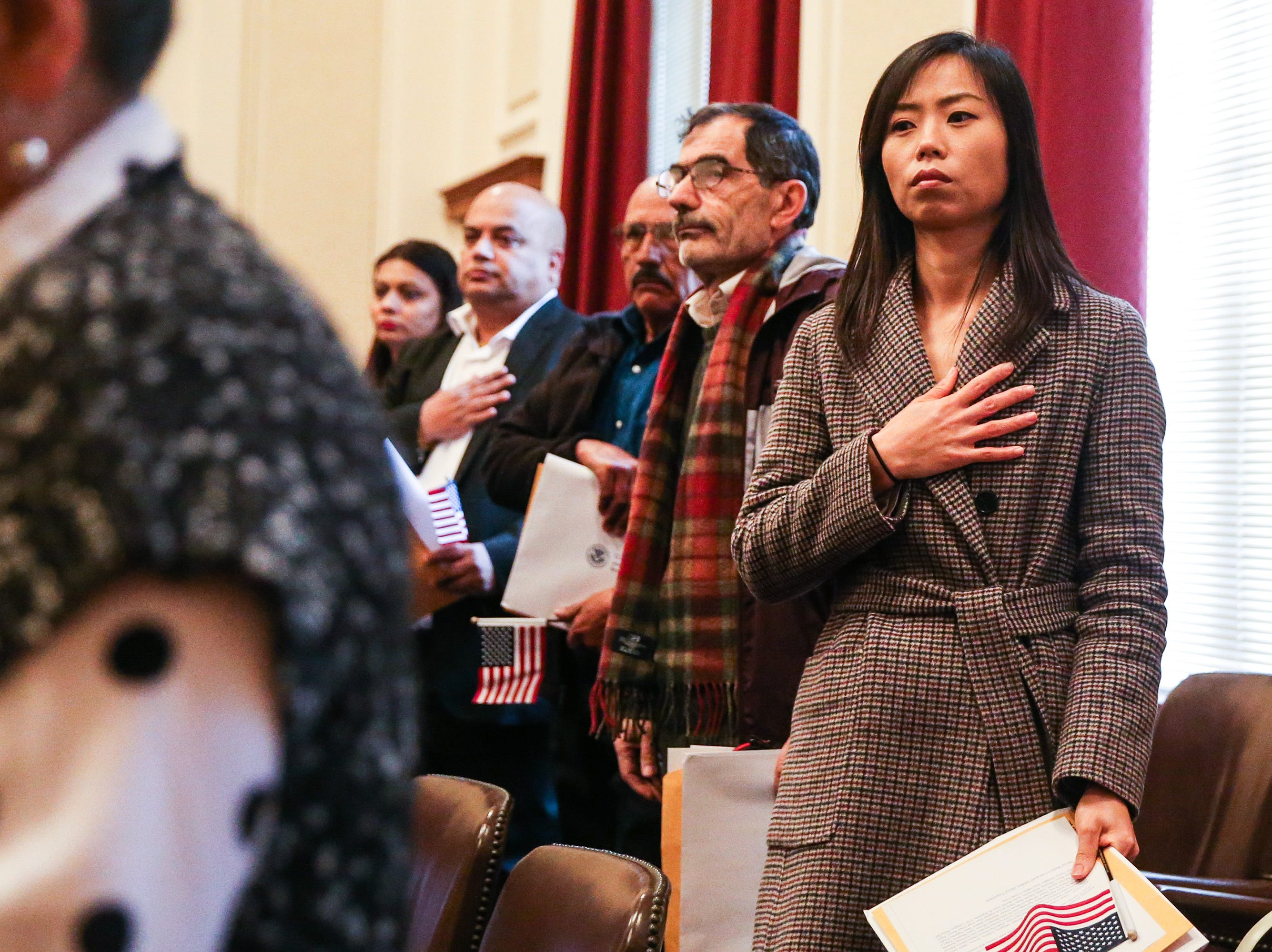 Eun Hye Kang and other applicants pledge allegiance during the naturalization ceremony Wednesday, Jan. 8, 2019, at the O.C. Fisher Federal Building.