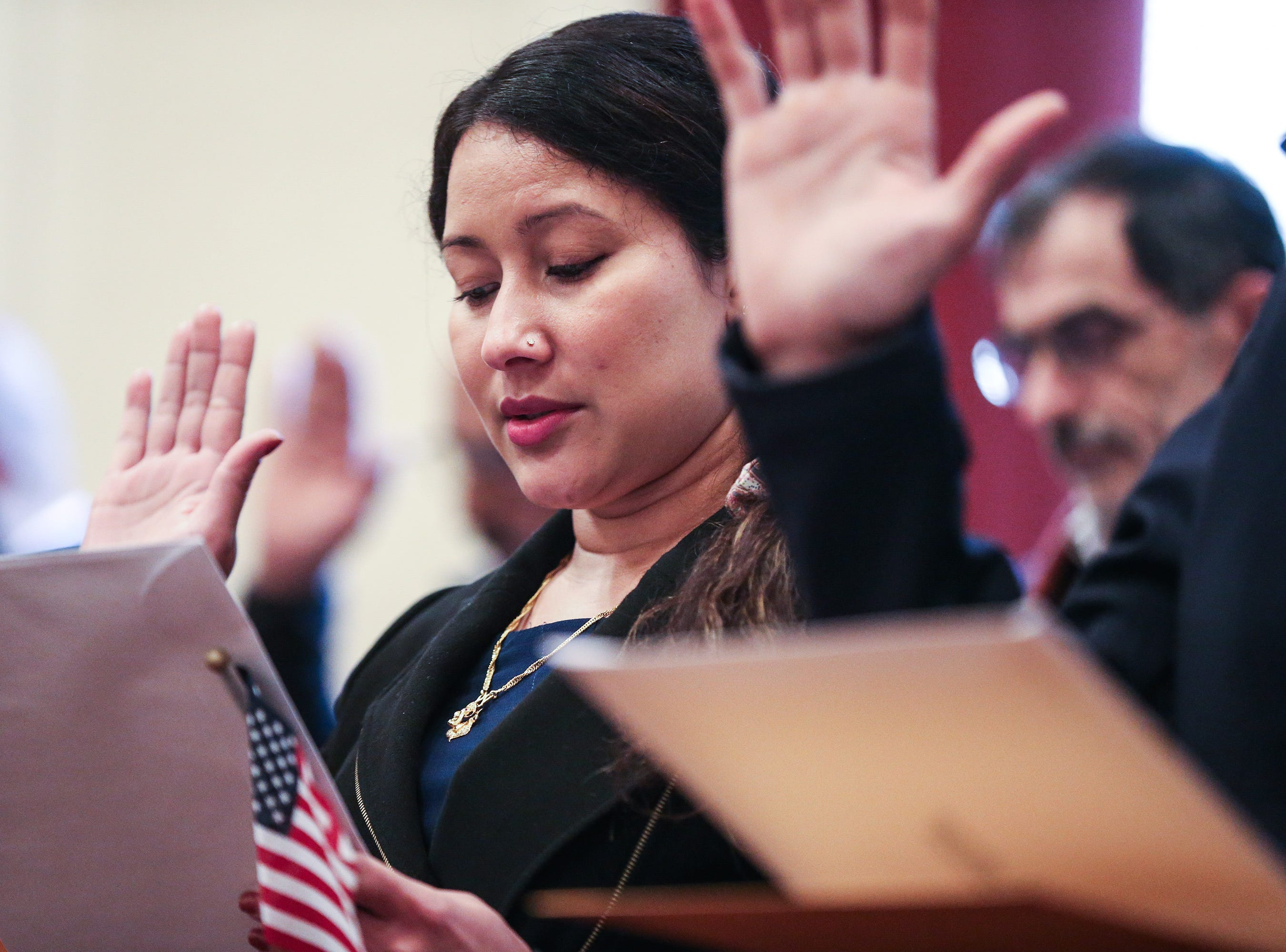 Sushmita Karki Niraula takes an oath during the naturalization ceremony Wednesday, Jan. 8, 2019, at the O.C. Fisher Federal Building.