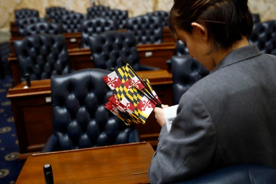 Page Emily Wells prepares to place Maryland state flags on desks in the Maryland House of Delegates chamber in Annapolis on Wednesday, Jan. 9, the first day of the state's 2019 legislative session.