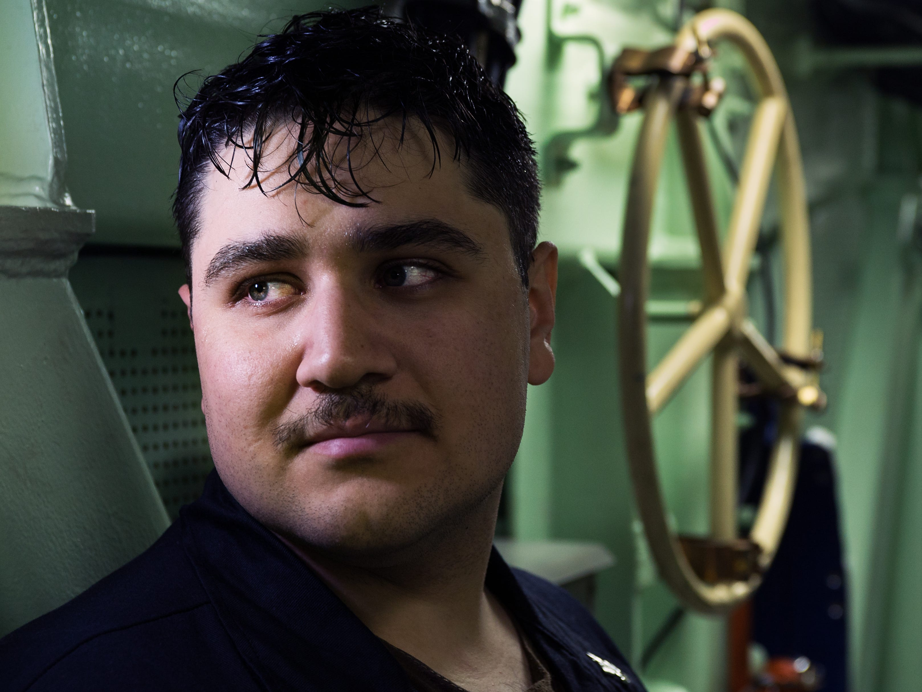 U.S. Navy Petty Officer 2nd Class Antonio Espinales, a Pre-commissioned Unit (PCU) South Dakota submariner, looks down a hallway during after a long shift during an underway somewhere in the Atlantic Ocean Nov 27.