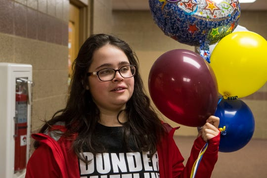 Mia Adams, one of the founders of student run business Tiger Balloons, delivers balloons to a student at Harrisburg High School, Wednesday, Jan. 9, 2019.