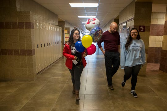 Mia Adams, left, Ryan Kroger and Angelynna Pyeatt deliver balloons to a student at Harrisburg High School, Wednesday, Jan. 9, 2019. The students started their own business, Tiger Balloons, in November 2017.