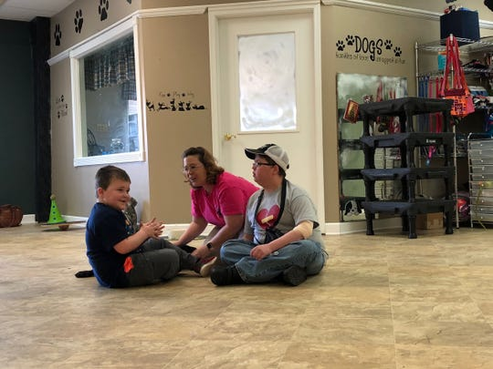 God's Canine Angels co-founder Stacey Payne sits with Noah Clarke, 6, and Jarod Davis, 20, on Jan. 5, 2019 to tell Clarke that she found him a service dog.