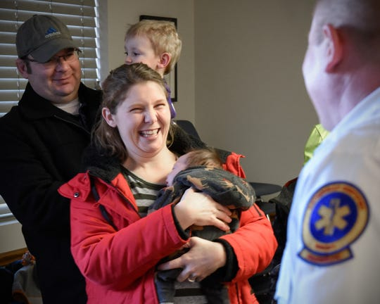 Katie Breth holds her son Trigg Wednesday, Jan. 9, as she talks with Gold Cross paramedics Kerin Helmke and Joel Peterson, who delivered him in the back of their ambulance Dec. 5.
