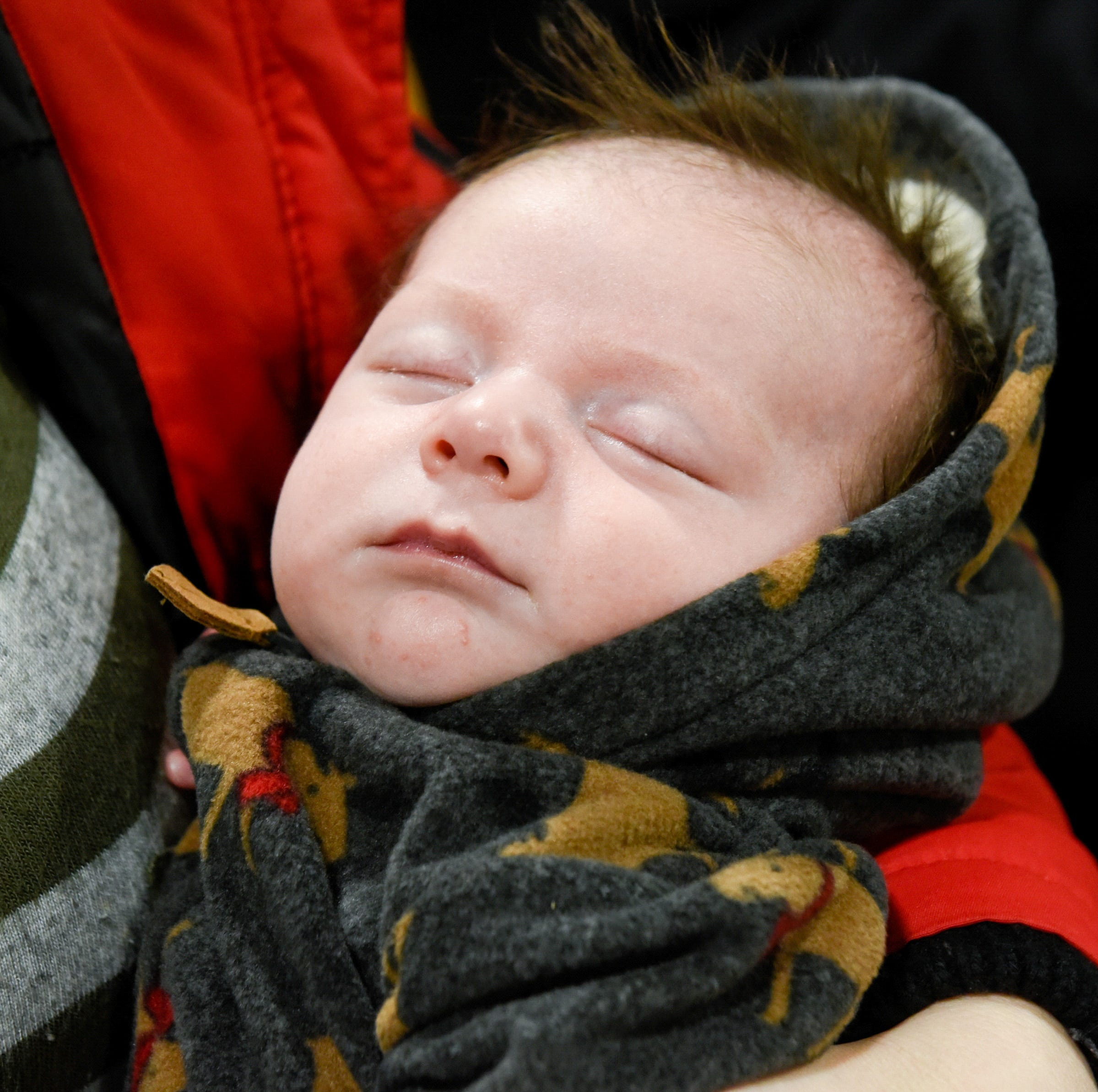 Trigg Breth sleeps through the festivities  Wednesday, Jan. 9, for Gold Cross paramedics Kerin Helmke and Joel Peterson, who delivered him in the back of their ambulance Dec. 5.
