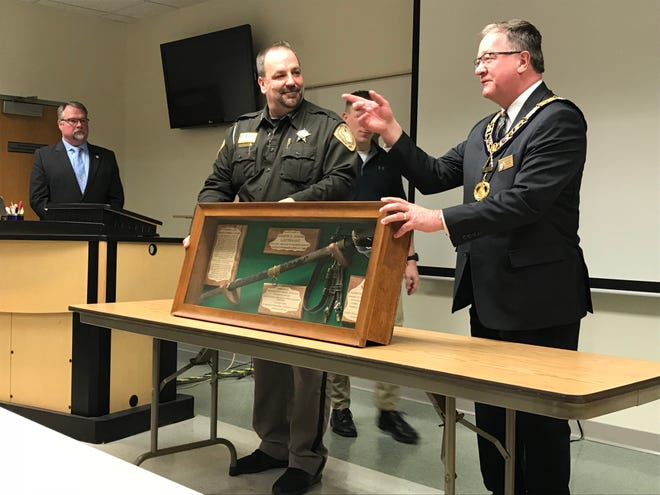 Portage County Sheriff Mike Lukas and Free Mason Grand Master Scott Pedley show Sheriff Joseph H. Baker's Civil War sword during a ceremony Wednesday at the Portage County Sheriff's Office.