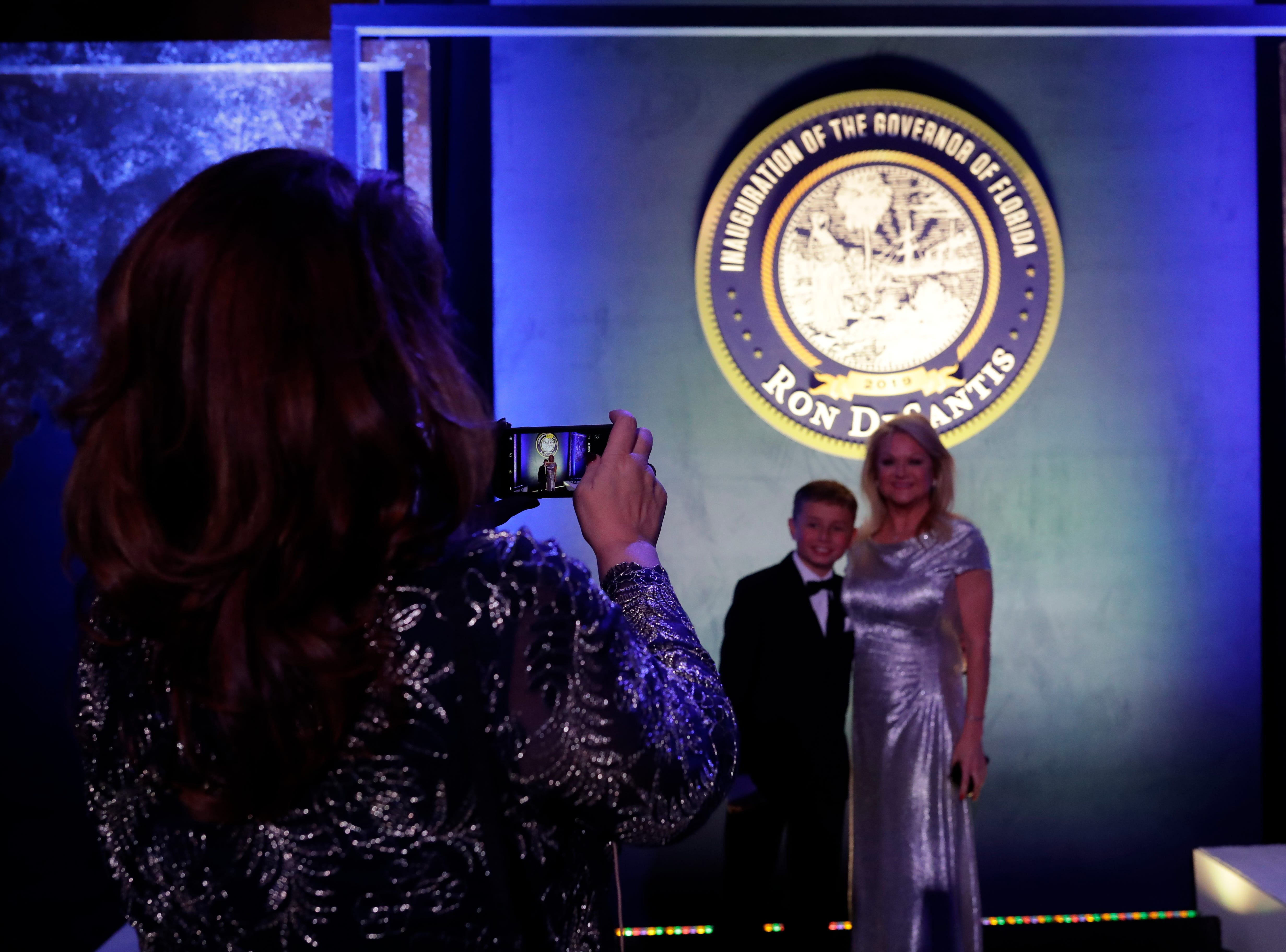 Hundreds of guests from all over Florida attend Florida's 46th Governor's Inaugural Ball at the Tucker Civic Center, Tuesday, Jan. 8, 2019. Guests pose for a photo in front of the DeSantis inauguration Florida state seal.