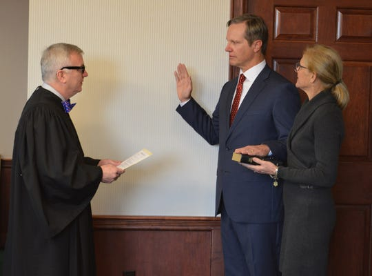 U.S. Chief Judge Mark Walker (L) swears in Larry Keefe as U.S. Attorney for the Northern District of Florida with his wife, Lynn, at his side.