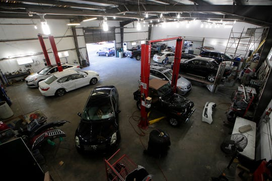 The body shop at Body Builders Paint and Body Inc. is full Wednesday, Jan. 9, 2019 as the business works to catch up after Hurricane Michael in October left them with a long line of customers waiting for vehicle repairs.
