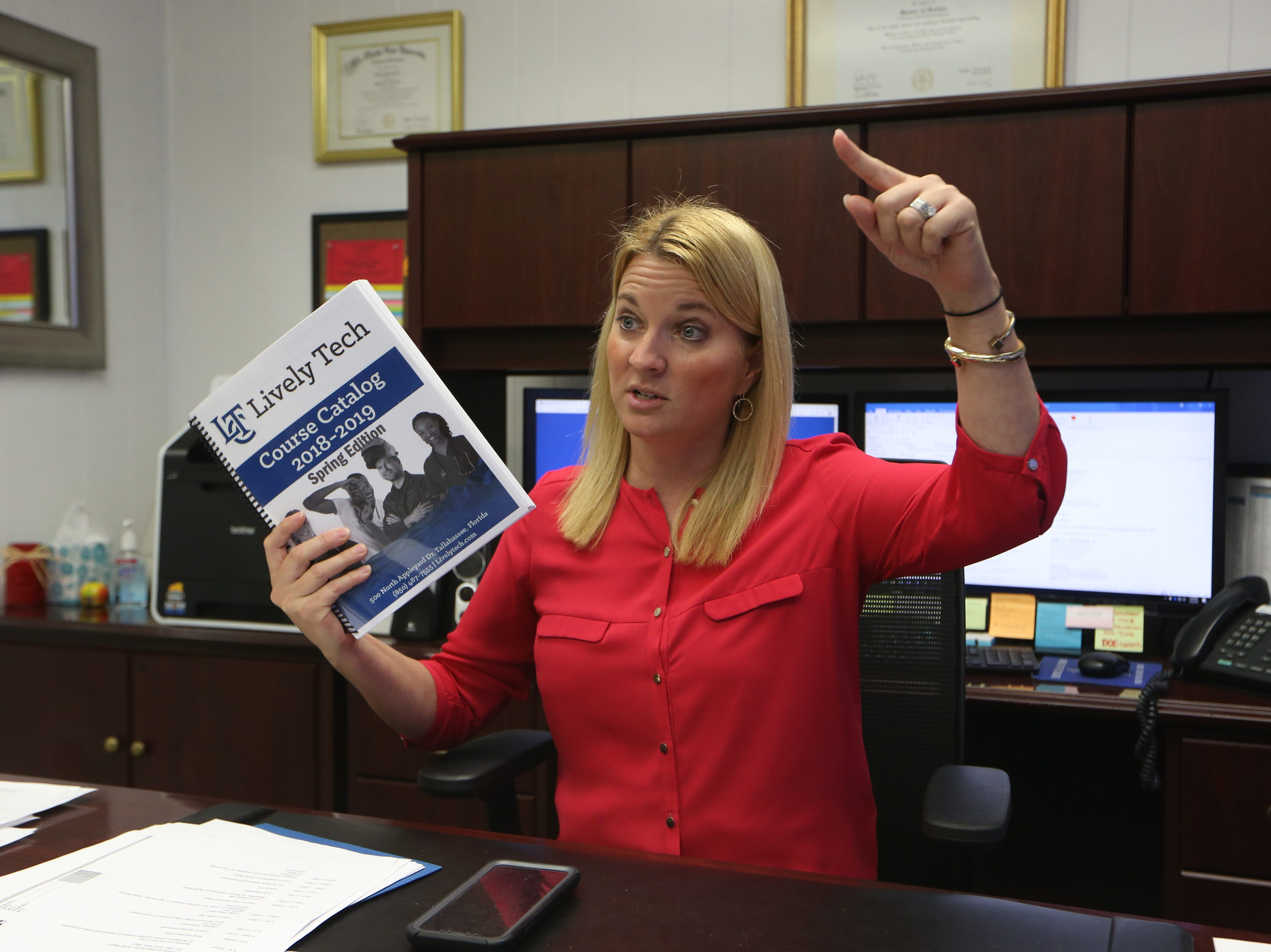 """Lively Technical Director of Career, Technical and Adult Education Shelly Bell holds up a course catalog that only reads """"Lively Tech"""" because when she assumed her position, she anticipated that Lively Technical Center would change its name to Lively Technical College. On Tuesday, Jan. 8, 2019, that change was approved by the Leon County School Board."""