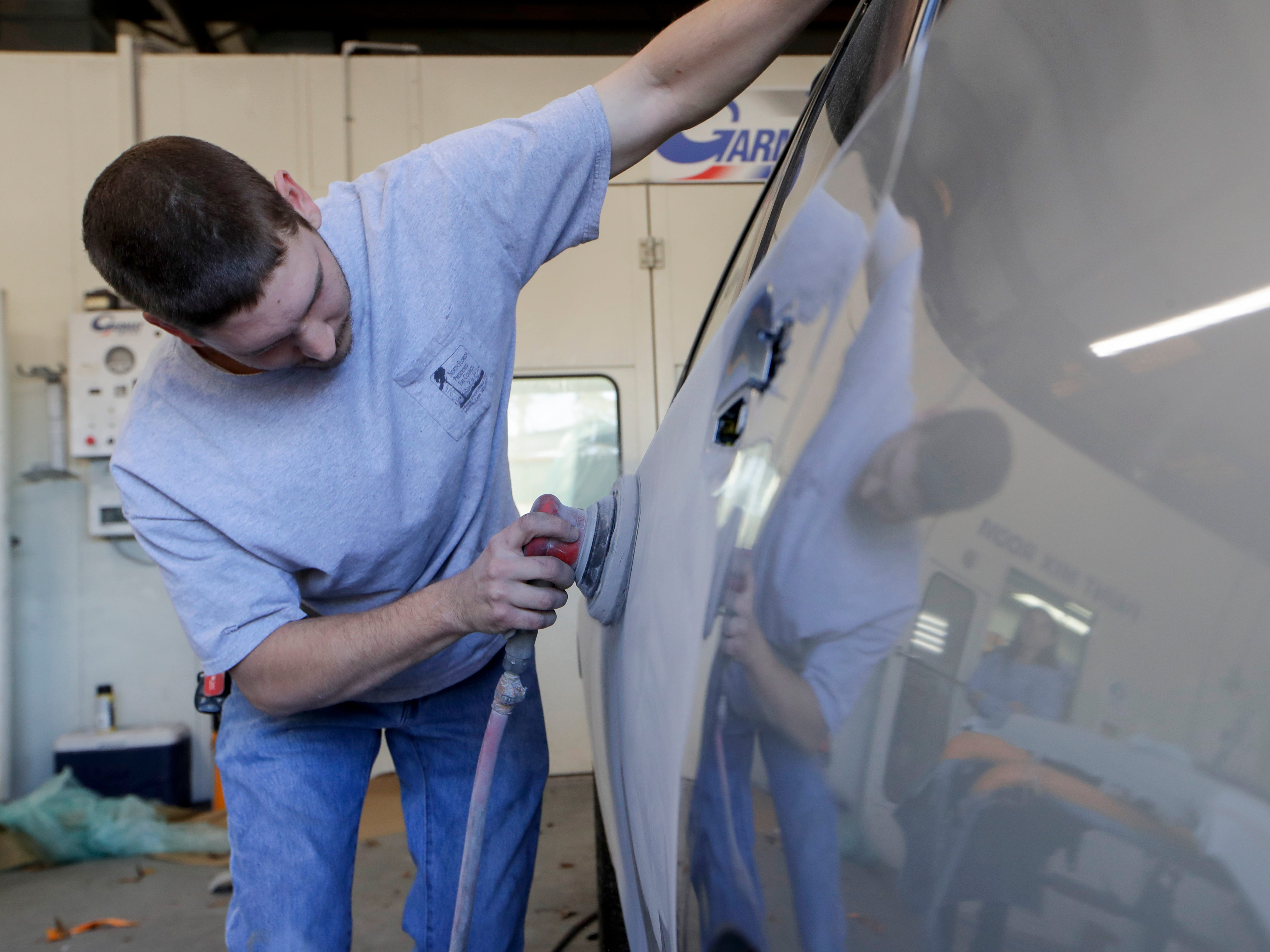 Body Builders Paint and Body Inc. paint prepper Christopher Roskowski sands down the paint on a Subaru that was brought to the body shop by a woman from Pensacola following Hurricane Michael after she was unable to find anyone there that could repair her vehicle.