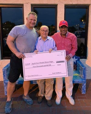Scott Van Duzer, left, with World War II veteran Pete Peterson, and Dr. Shamsher Singh hold a check for $9,000 raised for Southeast Florida Honor Flight from the VIP Golf Tournament.