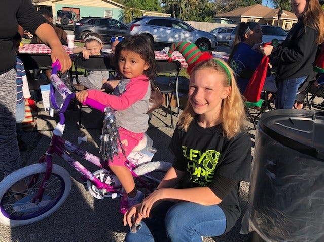 Elev8hope volunteer Paige Beams, right, helps this child pick out a bicycle at Elev8Hope's Community Christmas Toy Giveaway on Dec. 22 in Stuart.
