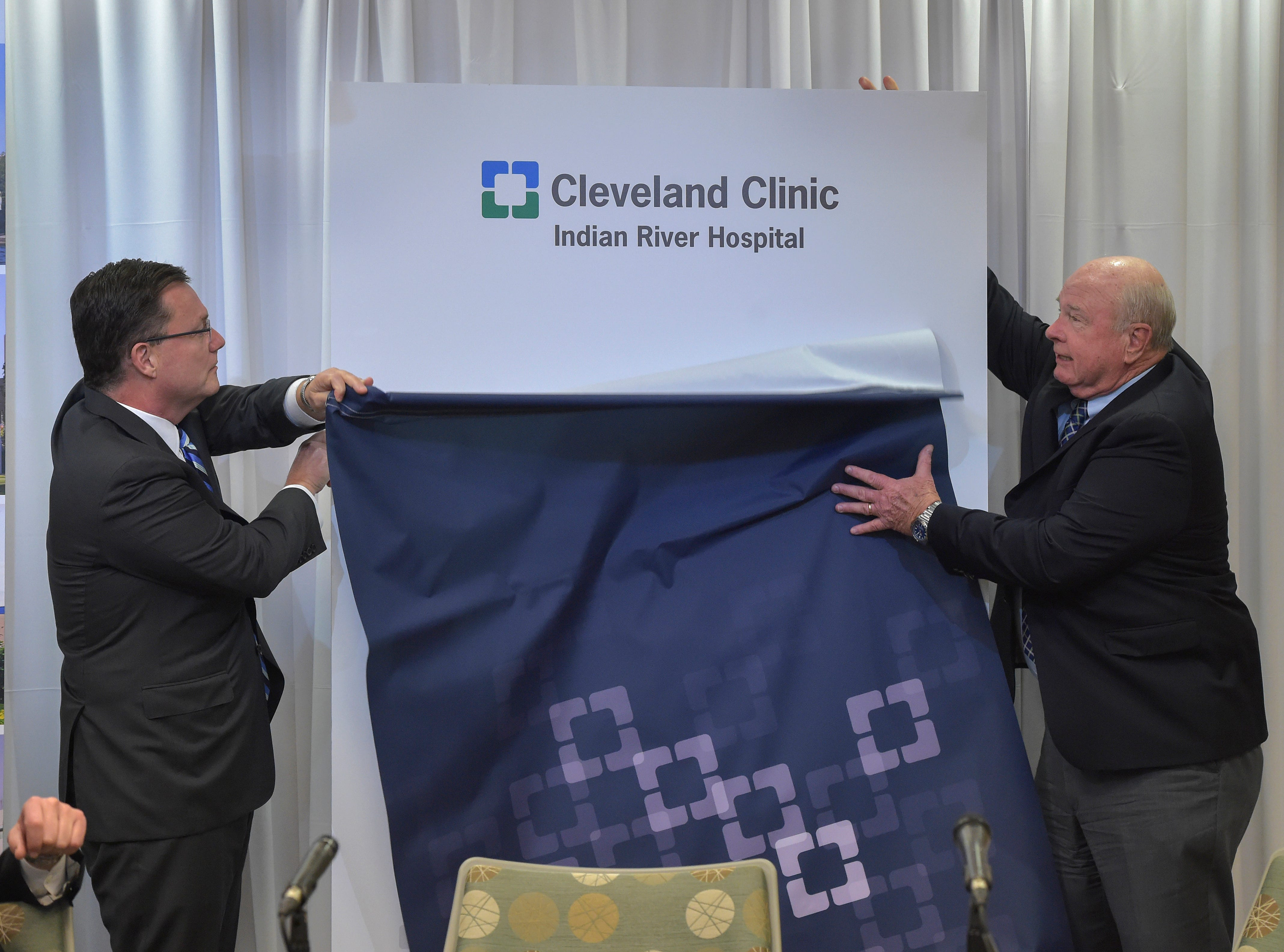 "Gregory Rosencrance, M.D. (left), President Cleveland Clinic Indian River Hospital, and Wayne Hockmeyer, Ph.D, Board Member, Cleveland Clinic Indian River Hospital, unveil their new name during a news conference at Cleveland Clinic Tradition Hospital in Port St. Lucie, Wednesday, Jan. 9, 2019, announcing the new names of Indian River Medical Center and Martin Health System. ""I think it's exciting, it's historic, frankly,"" Hockmeyer said.""It's a path we've been on for two years and now this is the culmination of a new start, part of the Cleveland Clinic."""