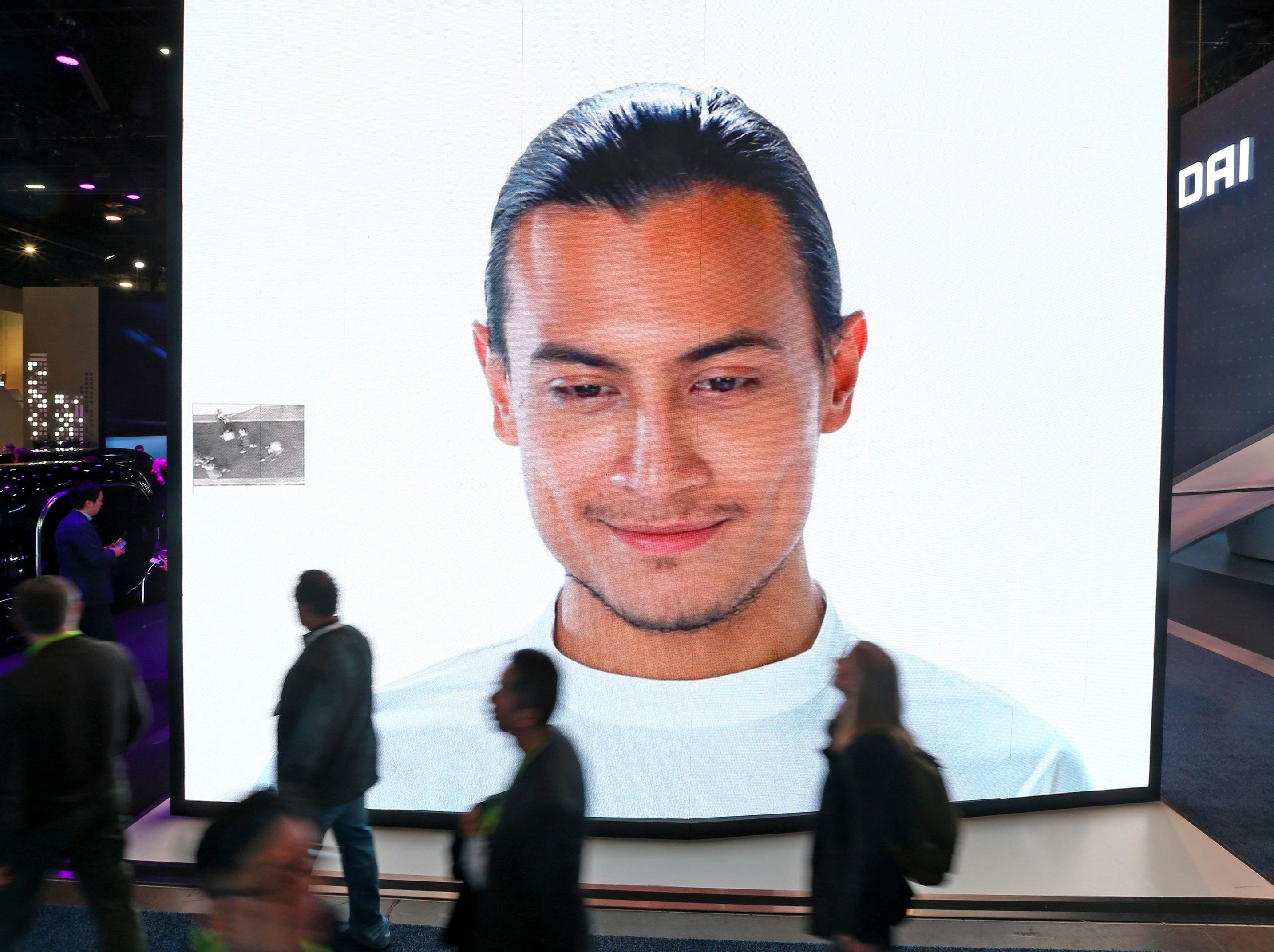 A giant KIA video screen advertises facial recognition in prototype vehicles as patrons walk past at CES International on Wednesday, Jan. 9, 2019, in Las Vegas.