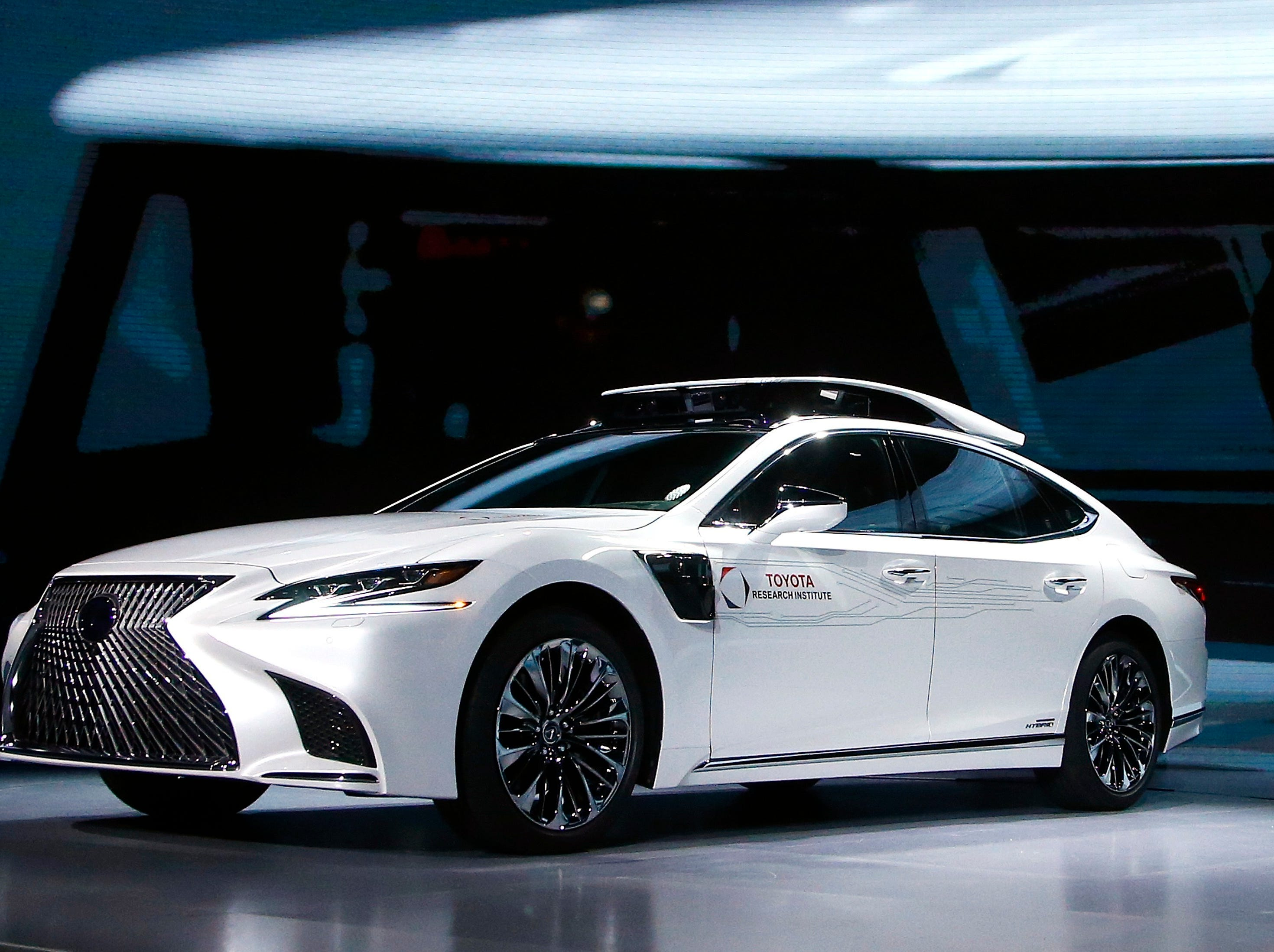 Toyota Research Institute, shows off Toyota's latest autonomous-driving test vehicle, called P4, based on the new-generation Lexus LS500h hybrid luxury sedan, with a roof-mounted assembly with cameras and sensors, and sensors added onto the front fenders, at the Toyota news conference at CES International on Monday, Jan. 7, 2019, in Las Vegas.