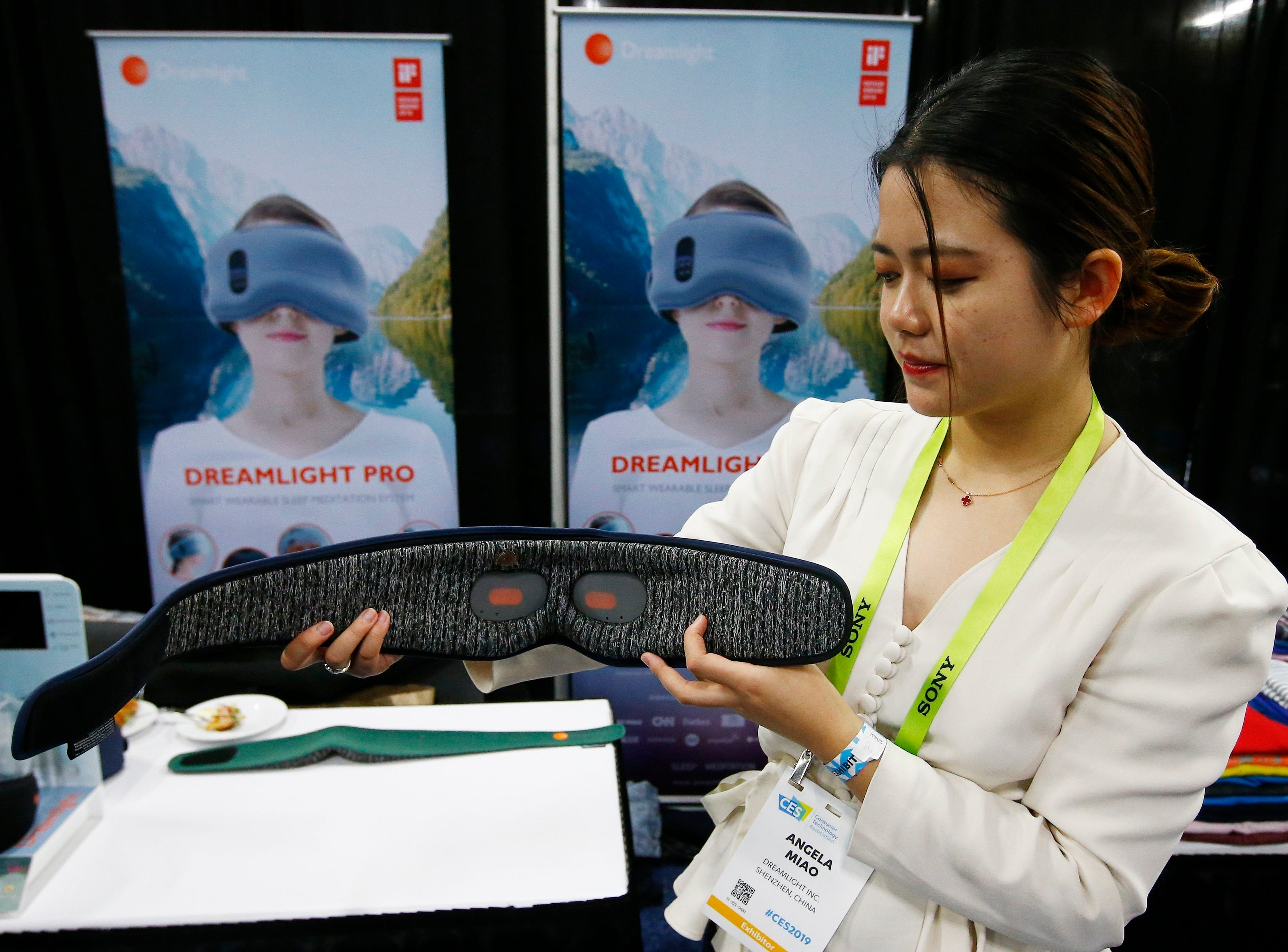 Angela Miao, of Dreamlight, demonstrates the new sleep mask Dreamlight Pro that uses light, sound and genetics so you fall asleep faster and wake up with more energy according to the company, at the CES Unveiled at CES International on Sunday, Jan. 6, 2019, in Las Vegas.