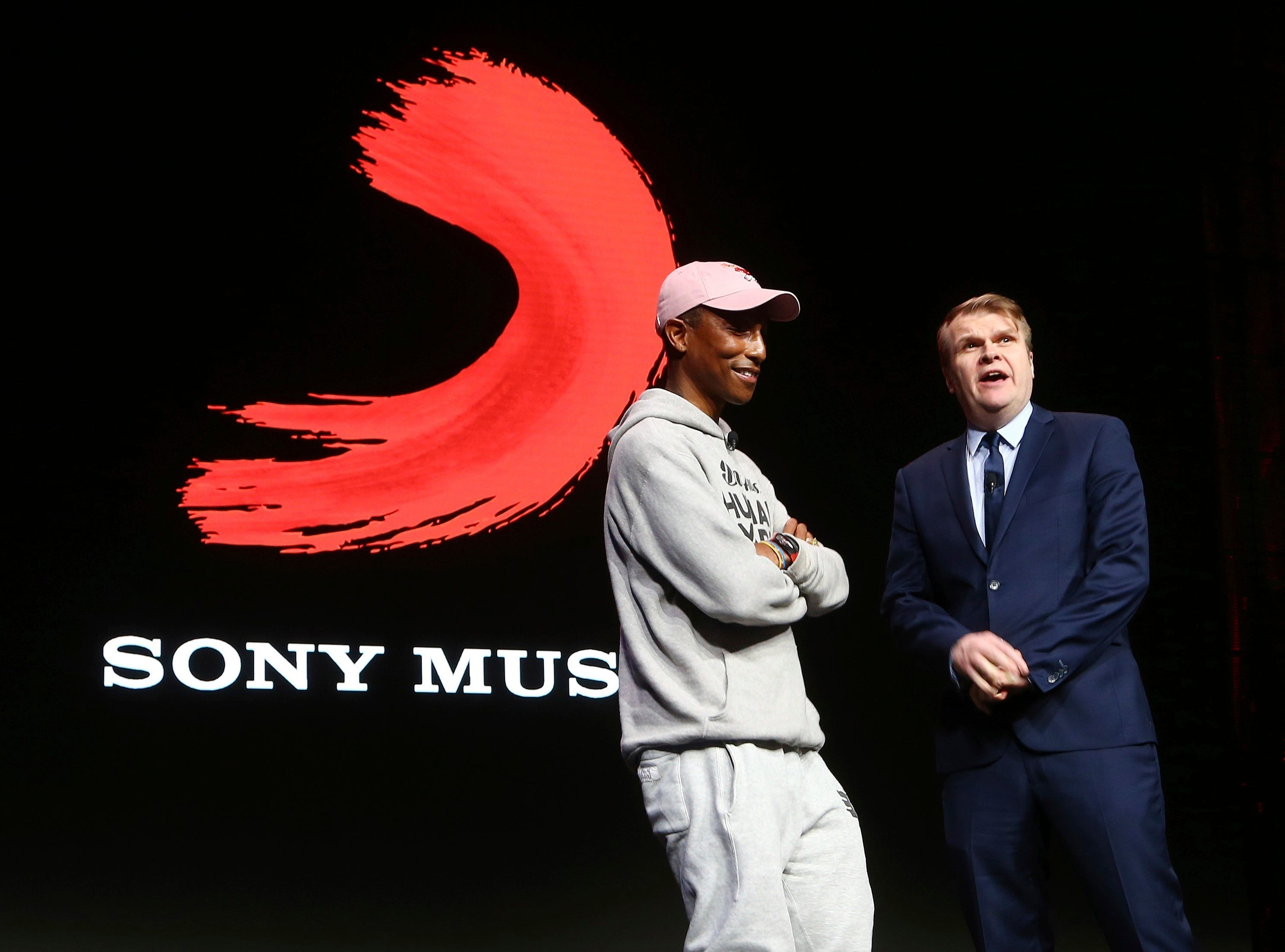 Rob Stringer, right, CEO of Sony Music Entertainment, surprises the audience as musician Pharrell Williams, left, walks on stage at the Sony news conference at CES International on Monday, Jan. 7, 2019, in Las Vegas.