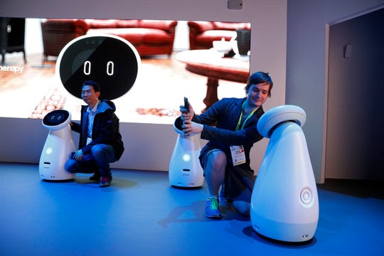Jason Stettner, right, takes a picture with a Bot Care robot in the Samsung booth at CES International on Tuesday, Jan. 8, 2019, in Las Vegas.