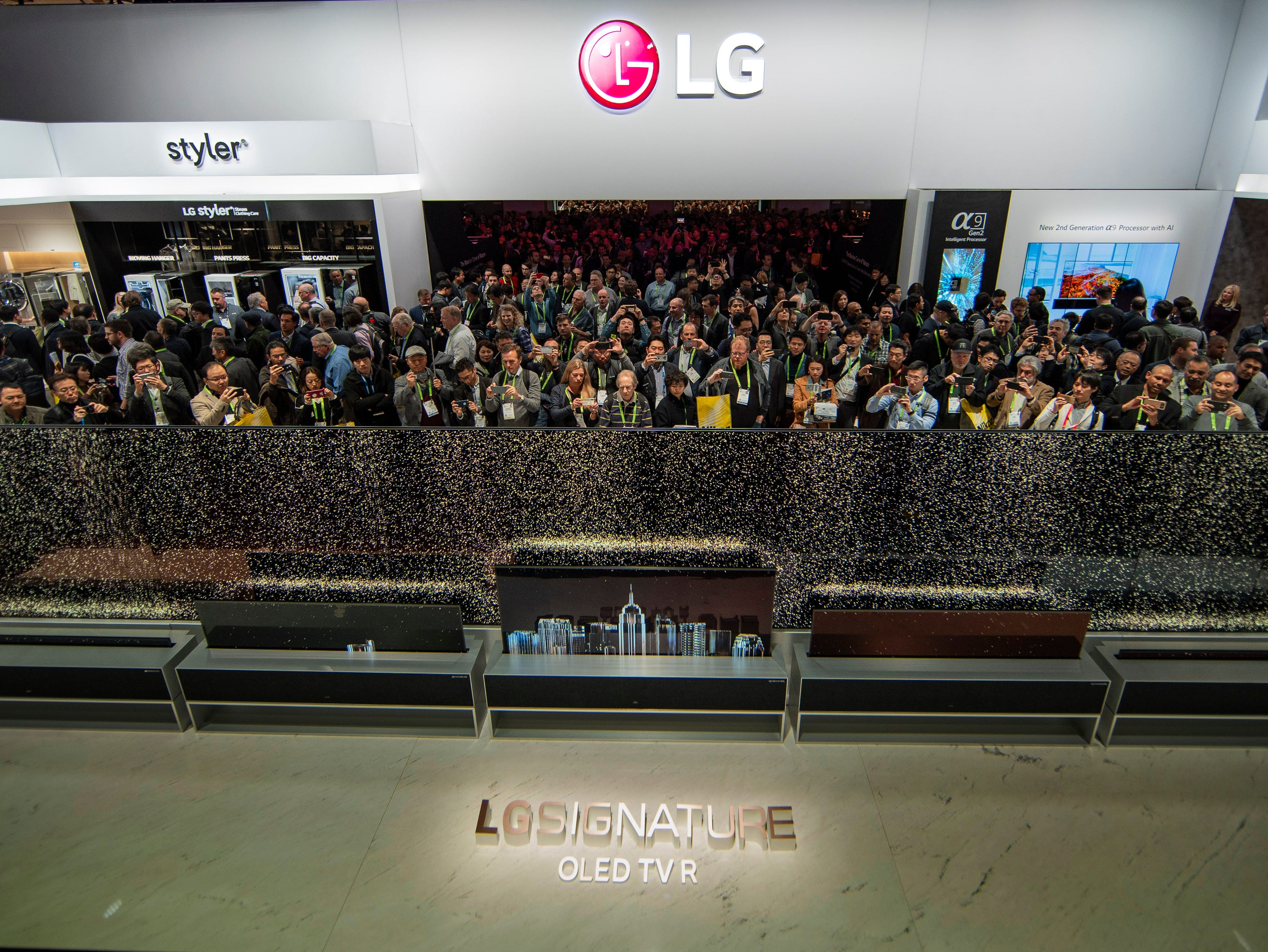 CES 2019 attendees get their first experience viewing the LG Signature OLED TV R, LG's rollable OLED TV at the LG Electronics booth Tuesday, Jan. 8, 2019, in Las Vegas.
