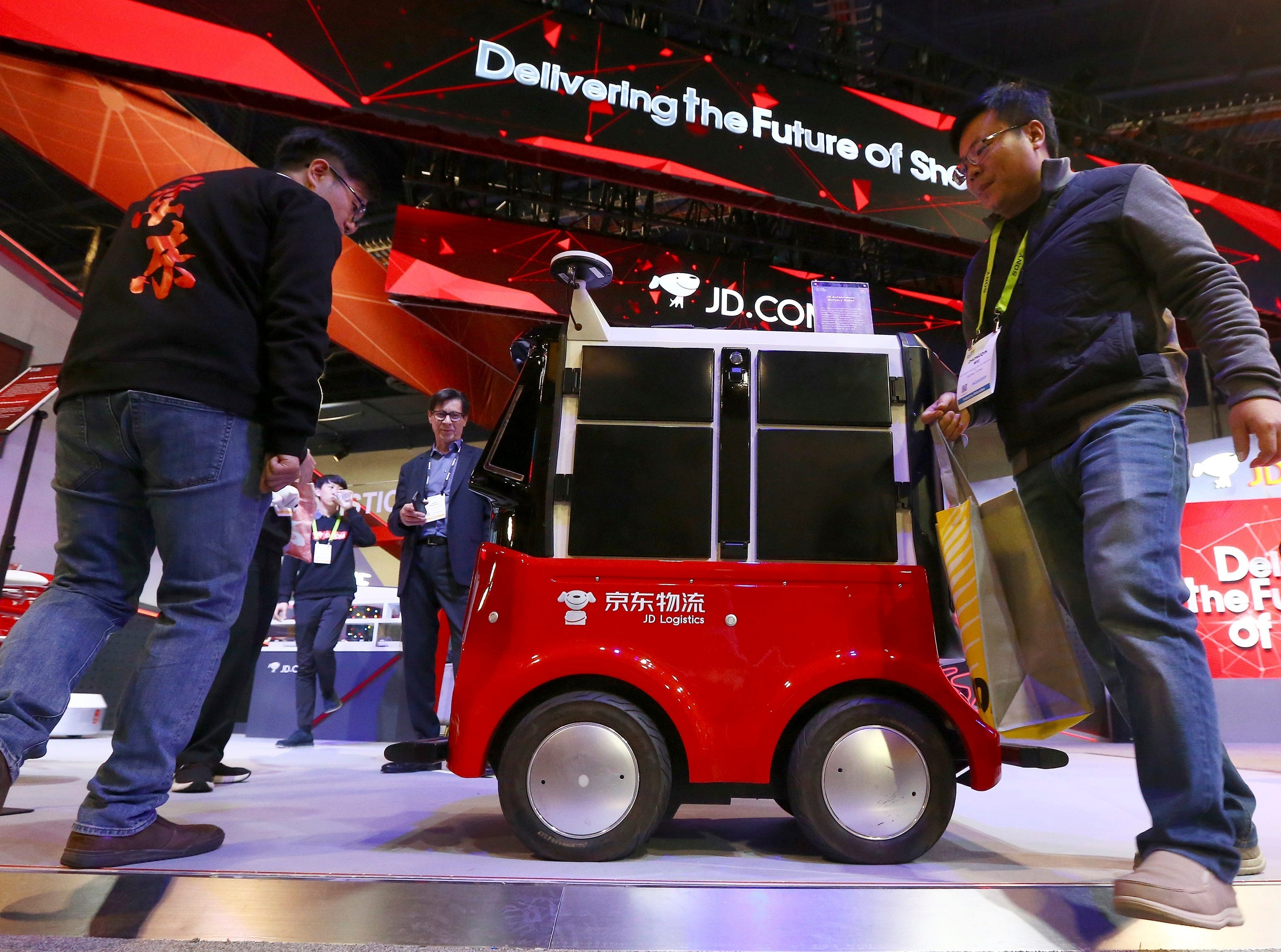 CES attendees check out the autonomous delivery robot vehicle at the JD.com booth at CES International on Tuesday, Jan. 8, 2019, in Las Vegas.