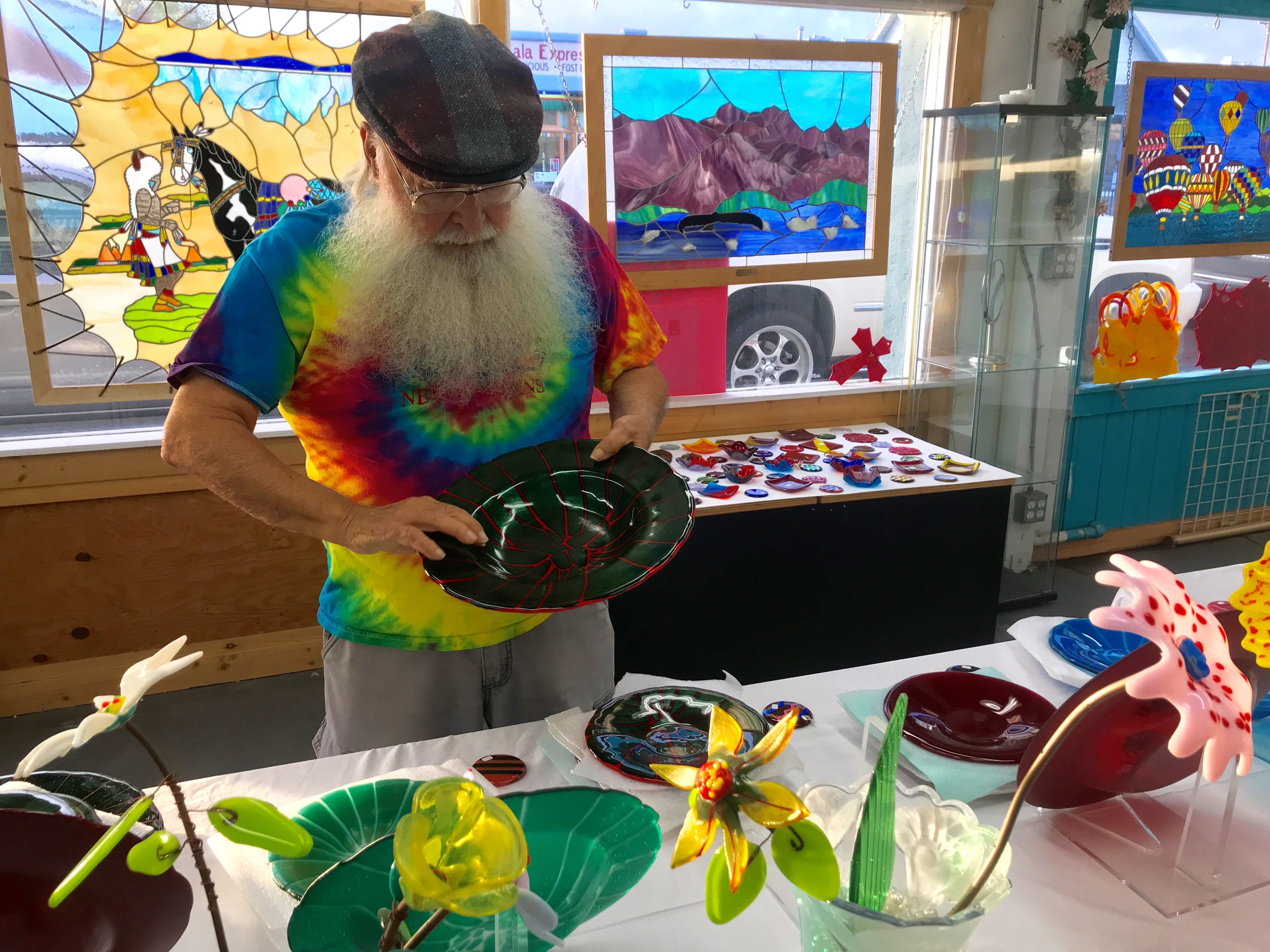 "Beglar ""Chief"" Merlich examines fused-glass bowls on display in his Bell Arts Factory studio, which will be closing at the end of the week."