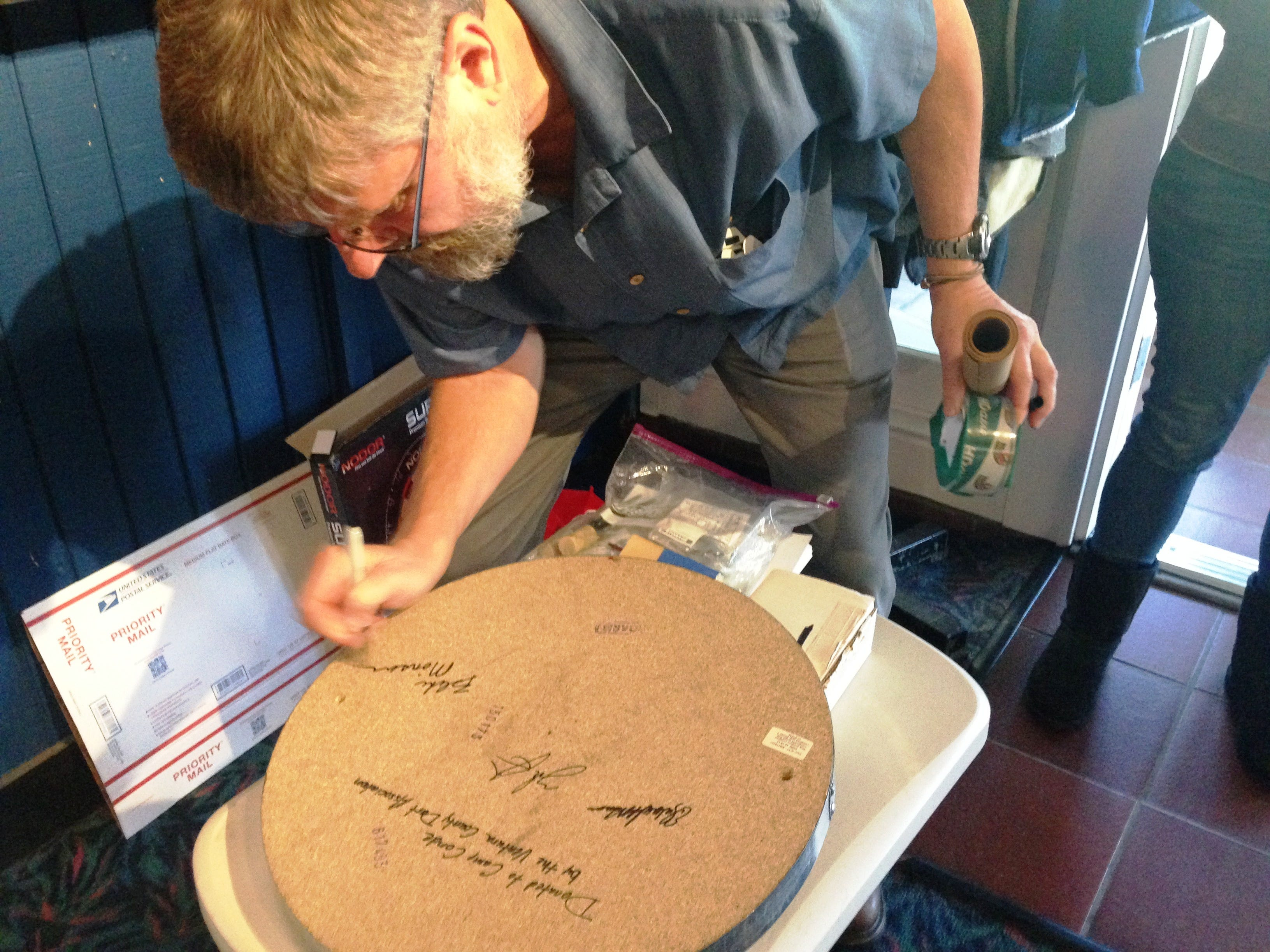 Blake Monson, webmaster of the Ventura County Dart Association, signs a tournament-quality dartboard that was donated by association members to deployed troops at Camp Conde in Afghanistan.