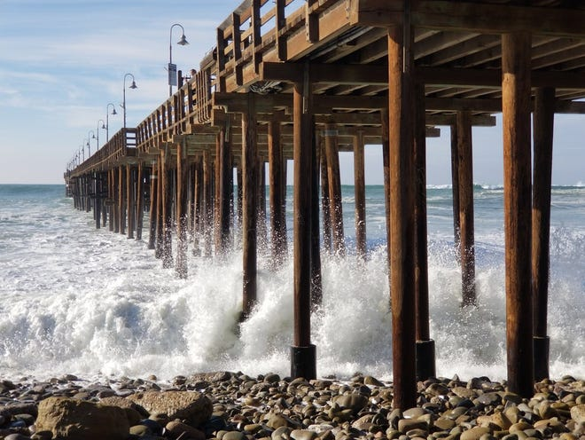 Waves crash under the Ventura Pier earlier this month. High surf Friday prompted the second closure of the pier this month.