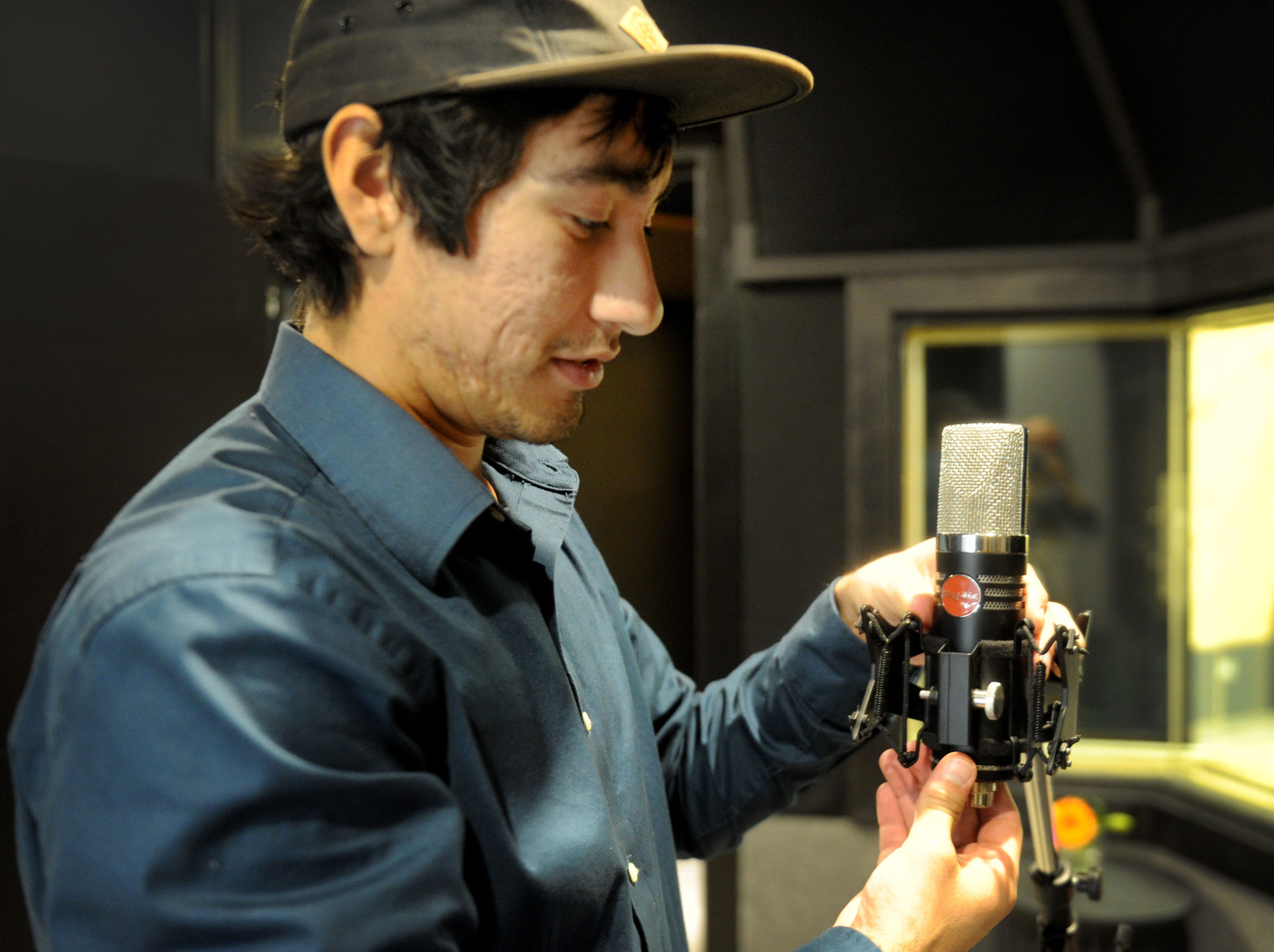 "Aaron Alvarez, a facility manager at Rose Lane Studios in Carpinteria, sets up a Mojave MA-1000 microphone for Andre ""Enyukay"" Rhodes, a Santa Barbara-based hip-hop artist."