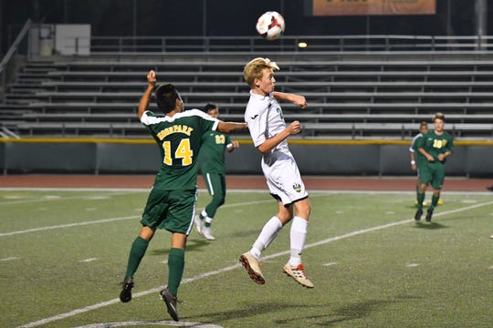 Thousand Oaks High's Connor Bumbarger attempts to win a header over Moorpark's Joel Aguillar during a nonleague match on Nov. 20. Moorpark won, 3-0.