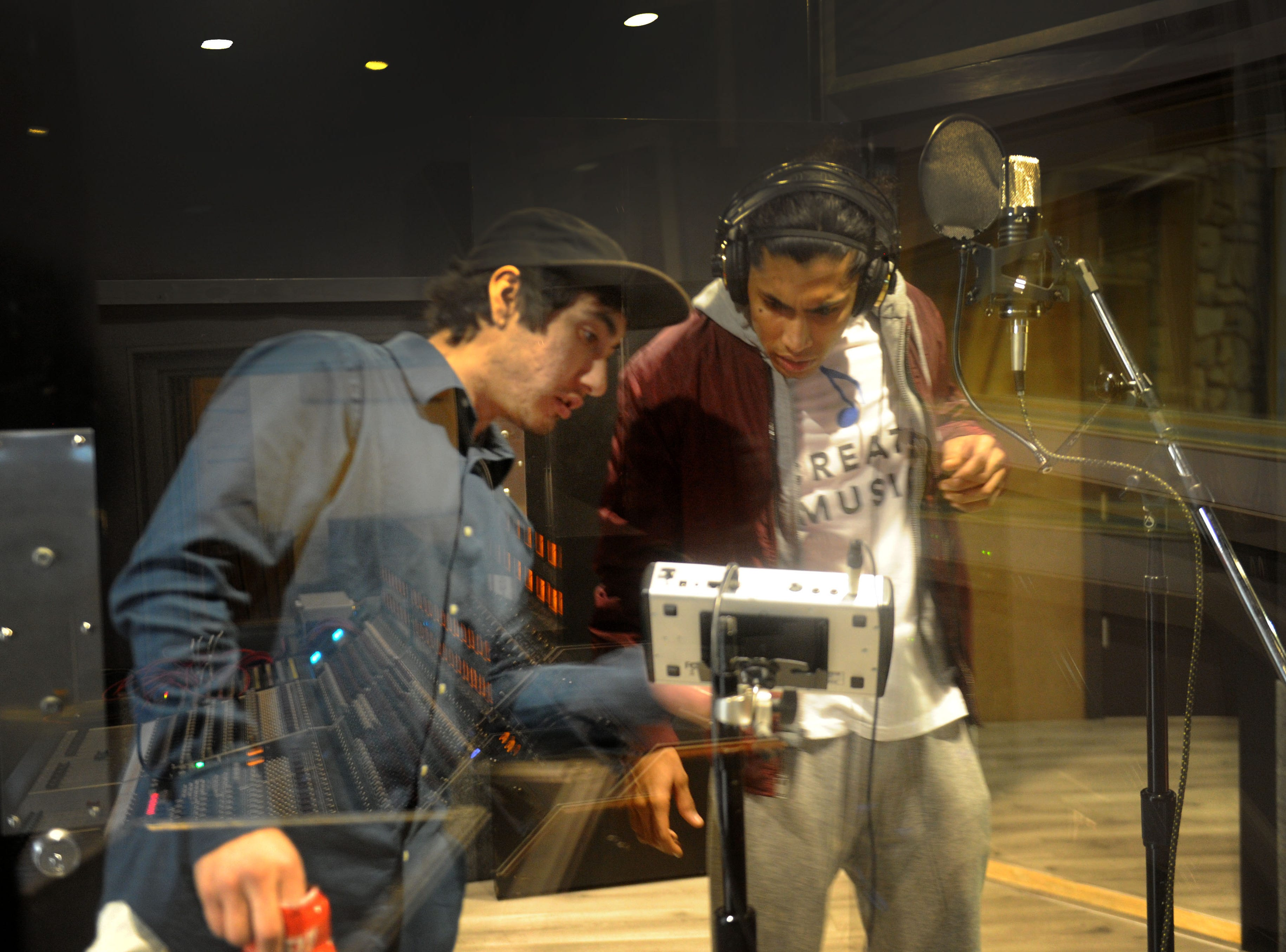 "Aaron Alvarez, left, the facility manager at Rose Lane Studios in Carpinteria, sets up Andre ""Enyukay"" Rhodes, a Santa Barbara-based hip-hop artist, with some headphones."