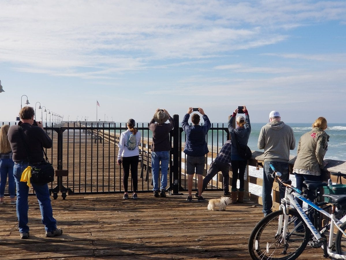 People take photos of the waves at the Ventura Pier Wednesday. High surf prompted city officials to close the pier.